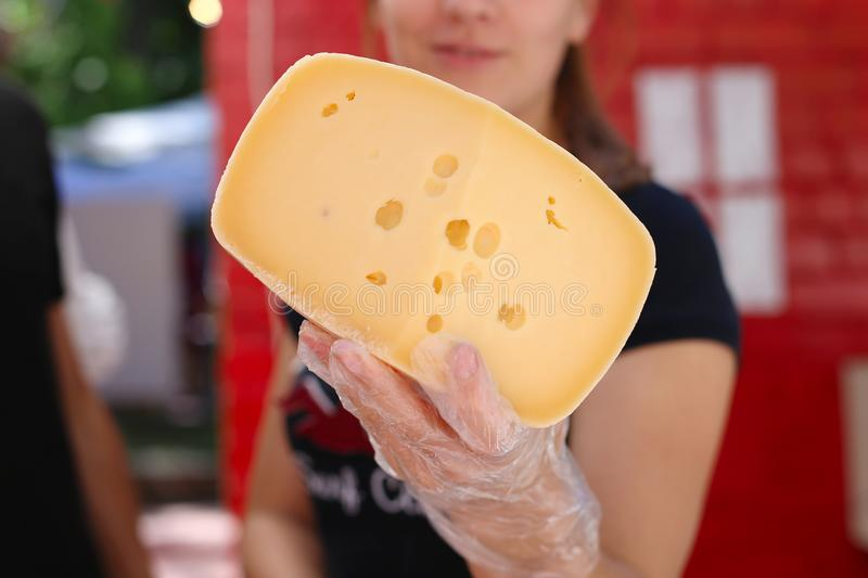 Girl is holding a large piece of hard cheese, homemade. royalty free stock photography