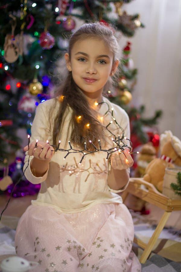 Girl holding lights over Christmas decoration stock photos