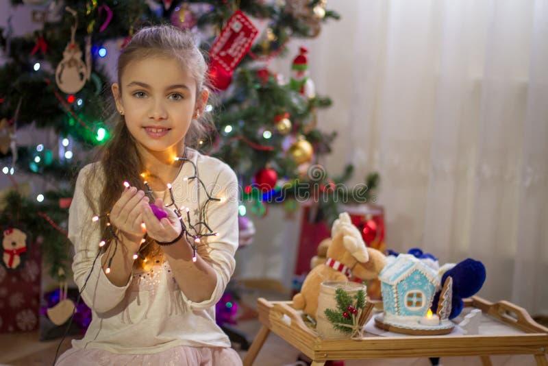 Girl holding lights over Christmas decoration stock photography
