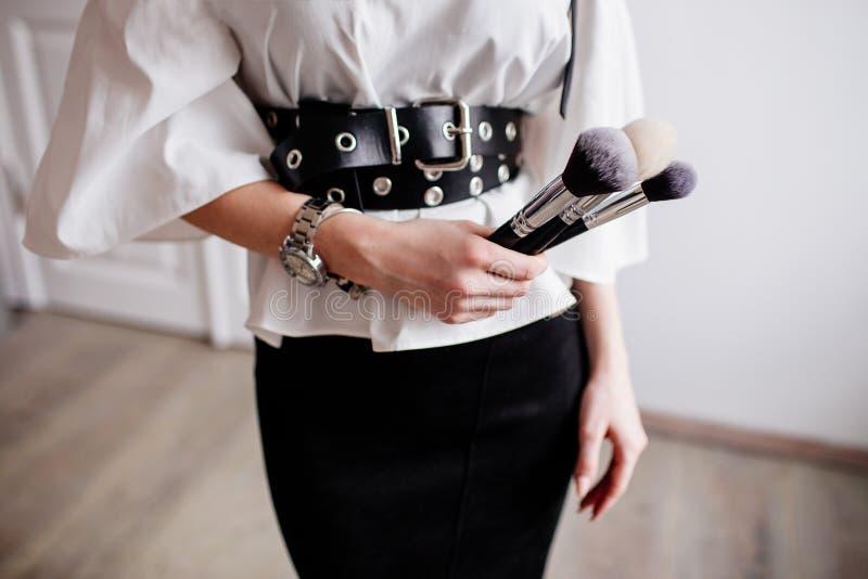 Girl holding make-up brushes. stock photos