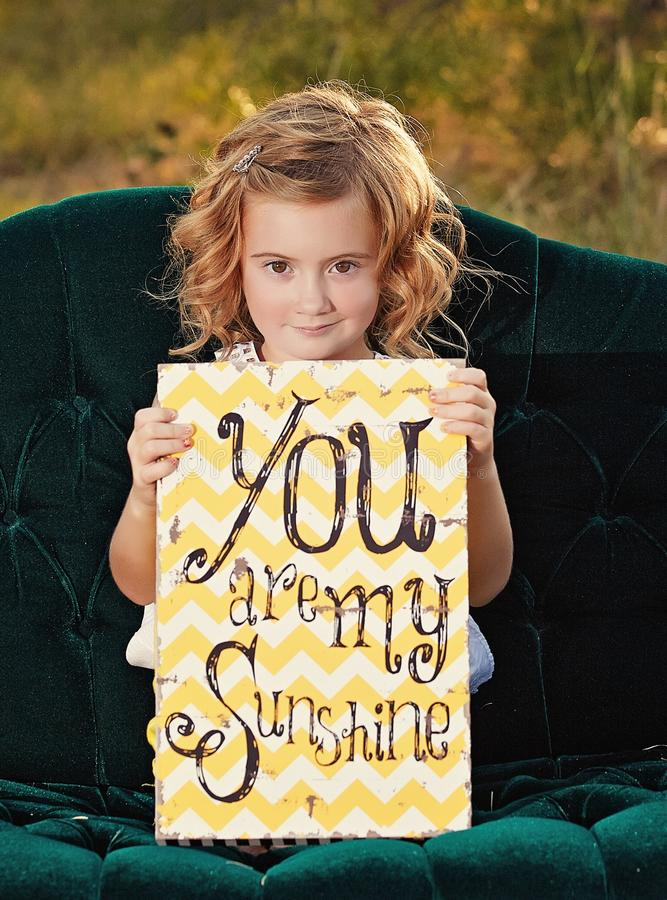Girl holding message board. Pretty little smiling blonde girl on sofa holding board with message 'you are my sunshine royalty free stock images