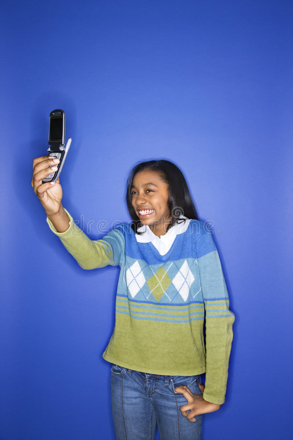 Girl holding out cellphone. Portrait of African-American teen girl taking photo with camera phone standing in front of blue background stock photos