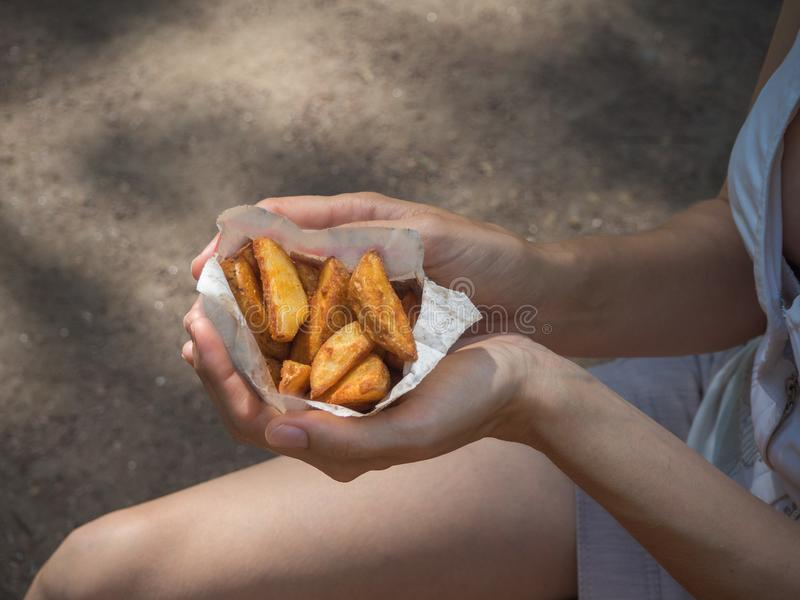A girl holding a pack of fries in hand in the street. Small pack of potato fries, fast snack royalty free stock photography