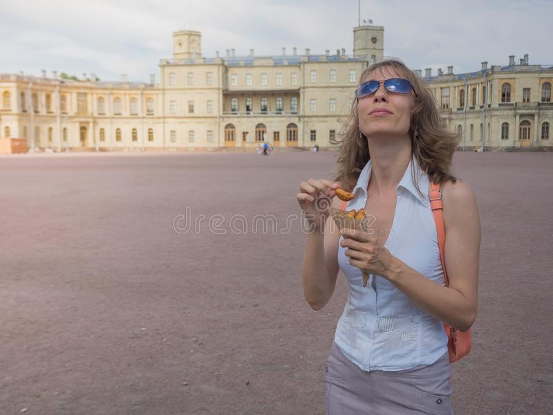 A girl holding a pack of fries in hand in the street. Small pack of potato fries, fast snack royalty free stock image