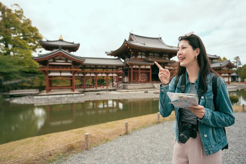 Girl holding paper map cheerfully pointing sky. Young girl holding paper map cheerfully pointing finger to blue sky while visiting in valley of the temples royalty free stock photo