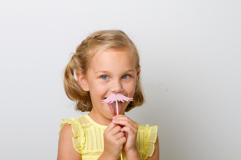 Girl holding paper party sticks on a solid background. Young preschool girl child holding paper mustache party sticks on a solid background royalty free stock image