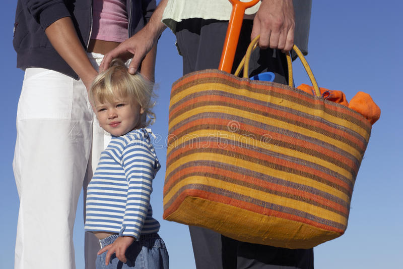Girl (2-4) holding parents hands, man carrying striped beach bag, mid-section, portrait. Girl (2-4) holding parents hands, men carrying striped beach bag, mid stock photos