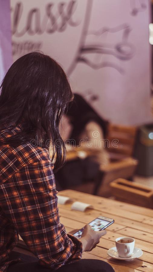 A girl holding phone while enjoying a cup of espresso macchiato in coffee shop stock image
