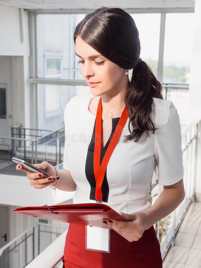 The girl is holding the phone in her hands. Beautiful Smiling Businesswoman Standing Against White Offices Background. Portrait of stock photos