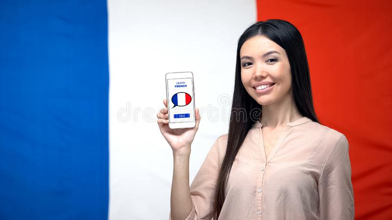 Girl holding phone with learn French application, flag on background, education. Stock photo royalty free stock images