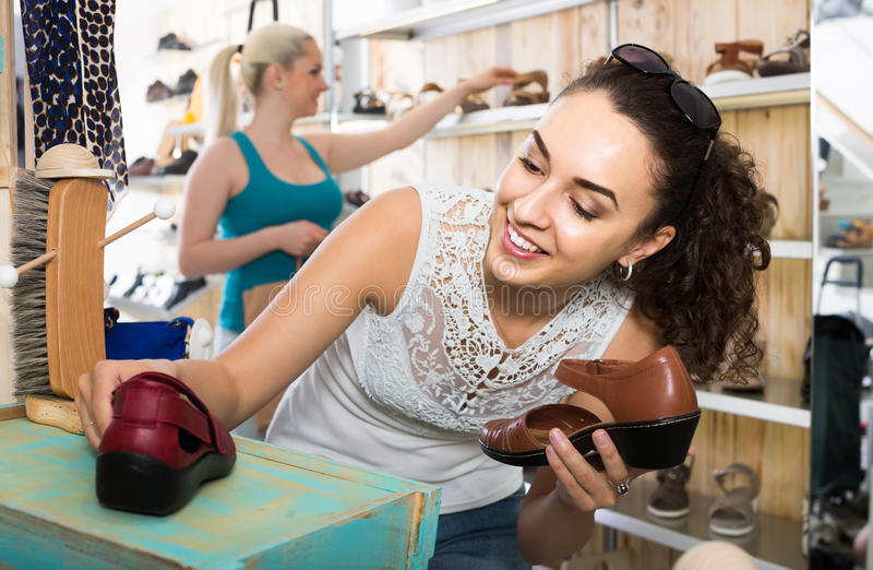 Girl holding a picked pair of shoes in the boutique stock images