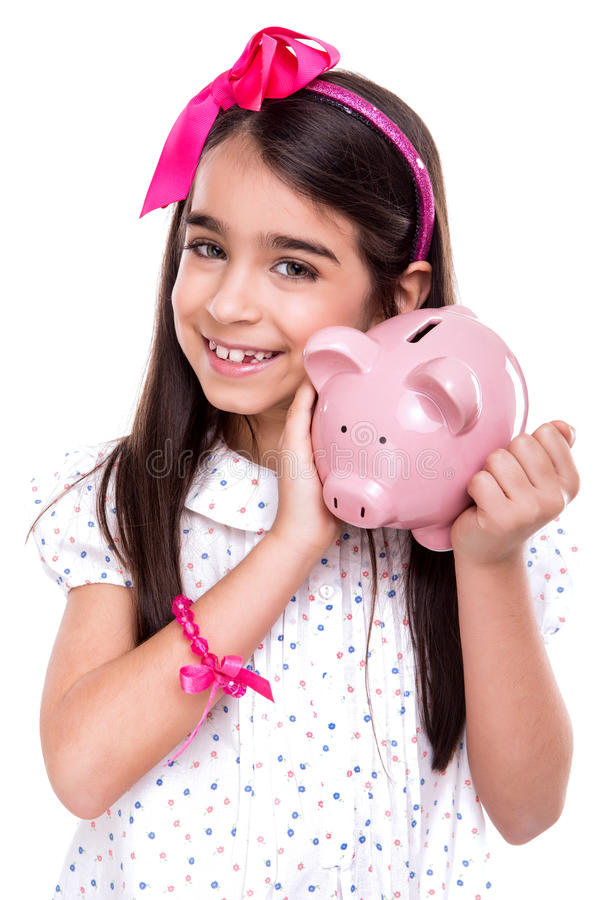 Girl holding a piggy bank. Young girl holding a piggy bank over white background royalty free stock image