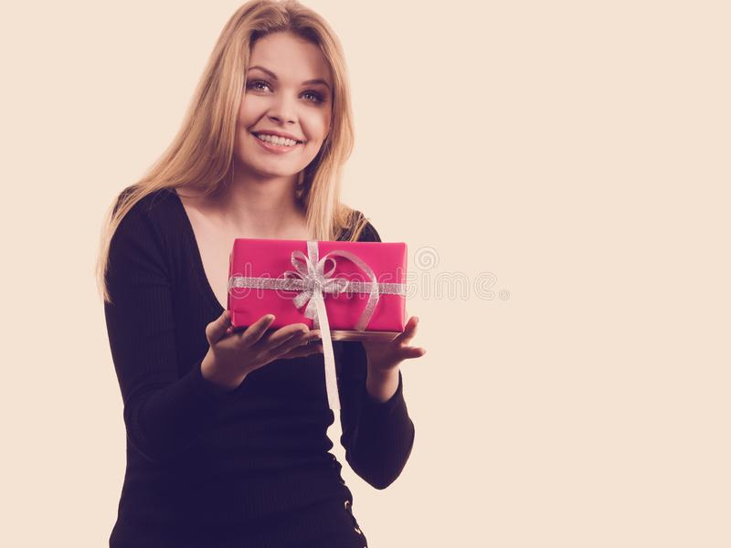 Girl holding pink gift box. People celebrating xmas love and happiness concept. Elegant blonde girl holding present pink gift box, on white stock photography