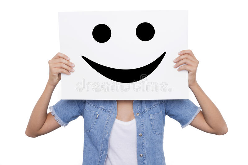 Girl holding a placard with a smiling smiles front of her face stock photography