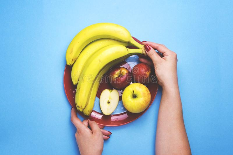 Girl holding a plate of fruit on a color background. The concept of healthy eating, diet royalty free stock image