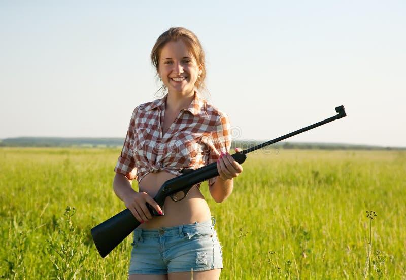 Girl holding pneumatic air rifle. Beautiful girl holding pneumatic air rifle outdoor royalty free stock photos