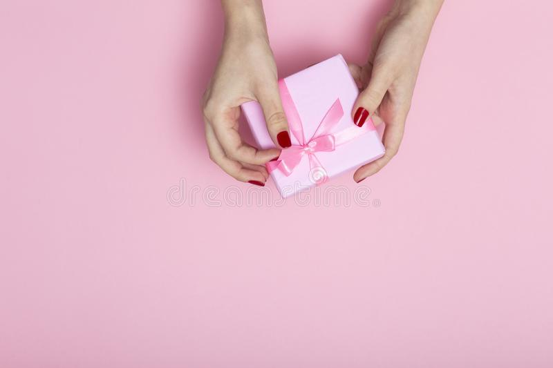 Girl holding a present in hands, women`s hands open the box wrapped in decorative paper on a pastel pink background, top view, royalty free stock images