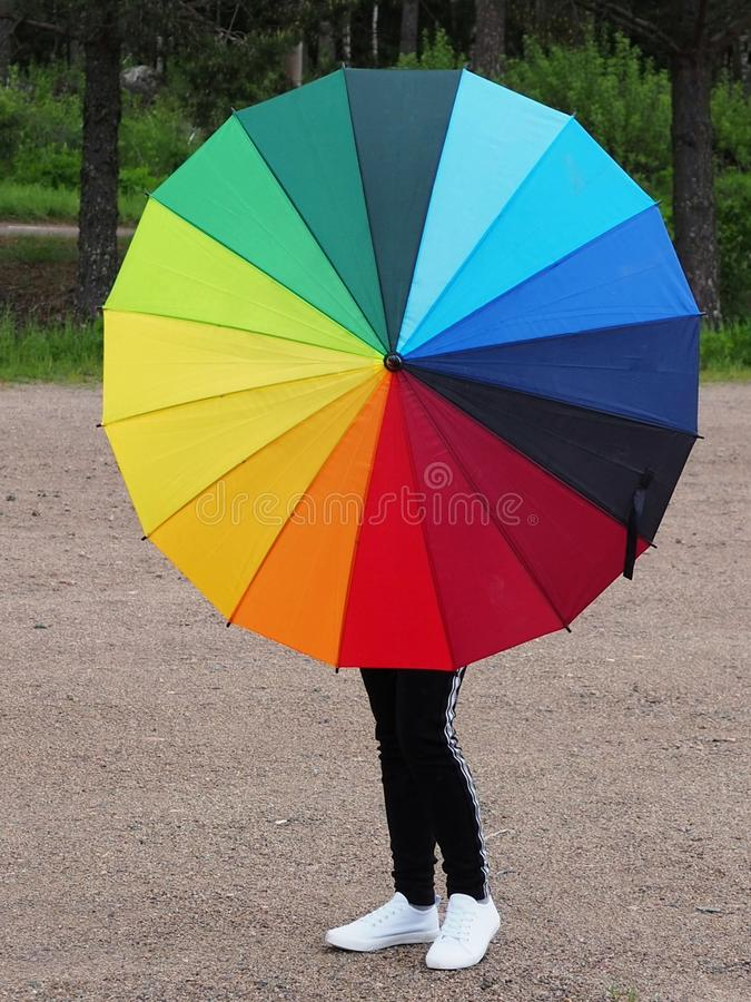 A girl holding a Rainbow coloured umbrella royalty free stock photography