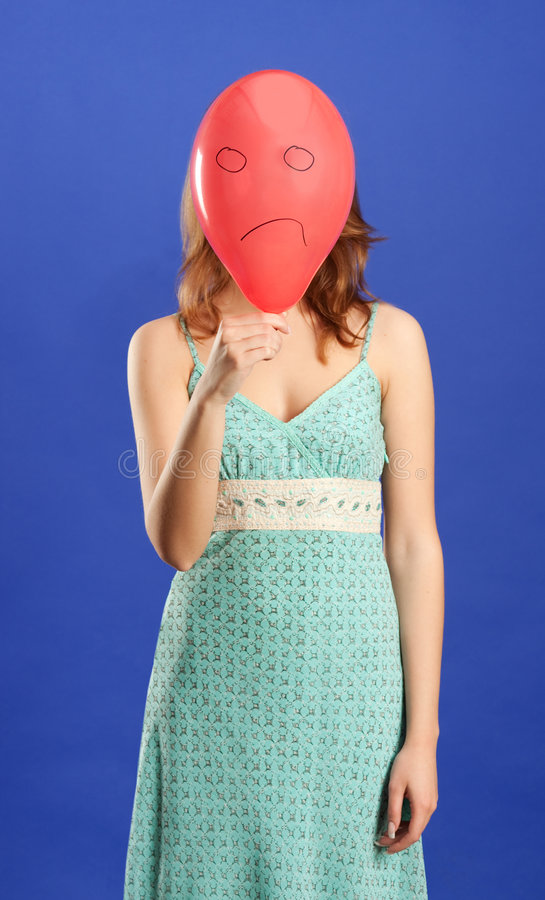 Girl holding red angry balloon stock photography