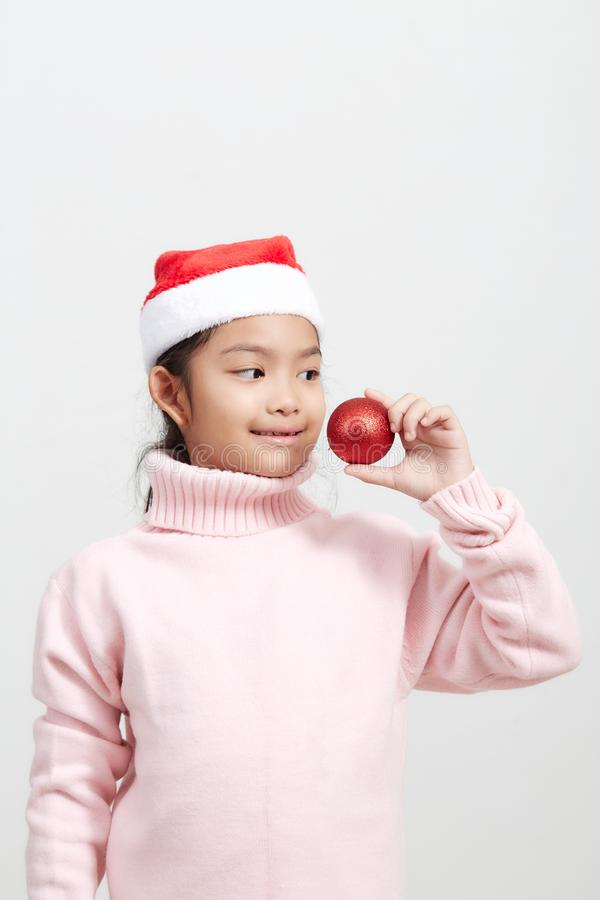 Girl holding a red christmas ball in sweater and santa hat stock images