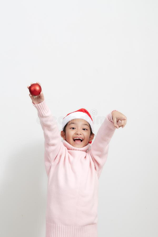 Girl holding a red christmas ball in sweater and santa hat royalty free stock photography