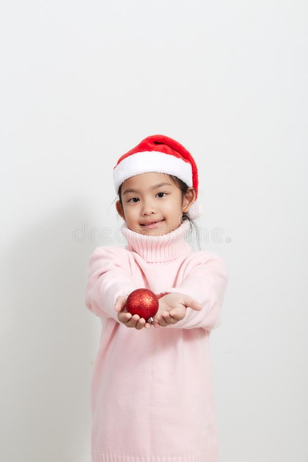Girl holding a red christmas ball in sweater and santa hat royalty free stock photos