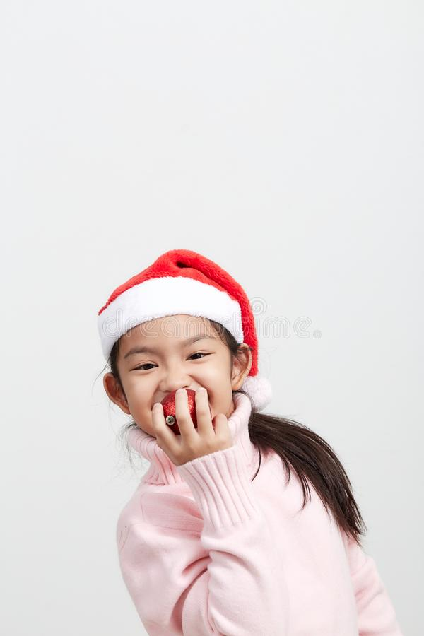 Girl holding a red christmas ball in sweater and santa hat royalty free stock image