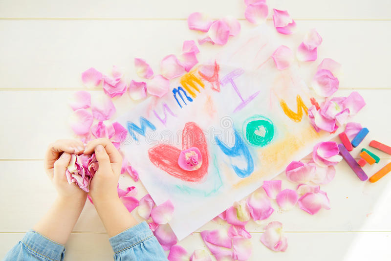 Girl Holding Rose Petals with Drawing for Mummy on the background. Girl Holding Rose Petals in her Hands with Drawing for Mummy on the background royalty free stock photo