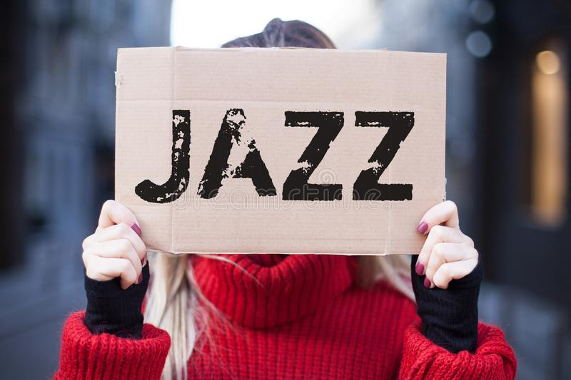 The girl is holding a sign with the inscription `Jazz royalty free stock image
