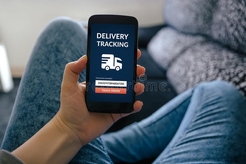 Girl holding smart phone with delivery tracking concept on scree royalty free stock photography