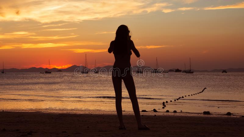 Girl holding smart phone and taking red sunset photo on the tropical beach.  Silhouette of a woman, yachts and mountains on royalty free stock image