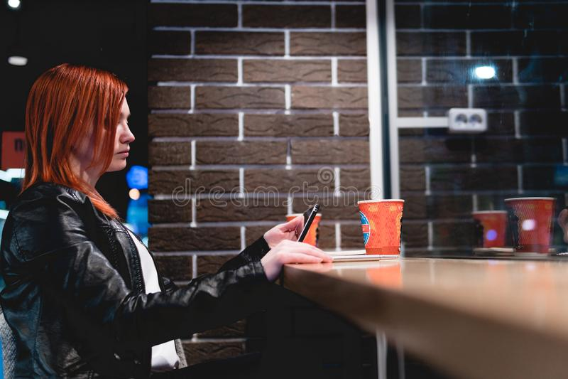 Girl holding smartphone in hand, sit in cafe, working, pen, use gadget. Network, wifi, social, communication. Freelancer works royalty free stock photography