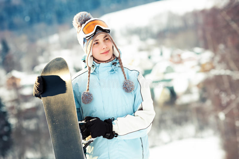 Girl holding snowboard. Young woman holding her snowboard, she's looking away and smiling, mountain village on background; copy space, close up royalty free stock images