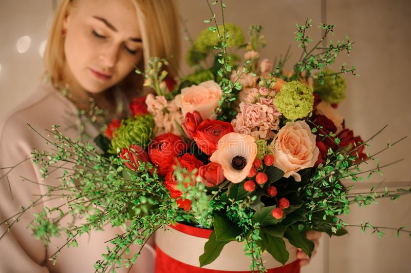 Girl holding a spring bouquet of tender peach color and passion red flowers royalty free stock image