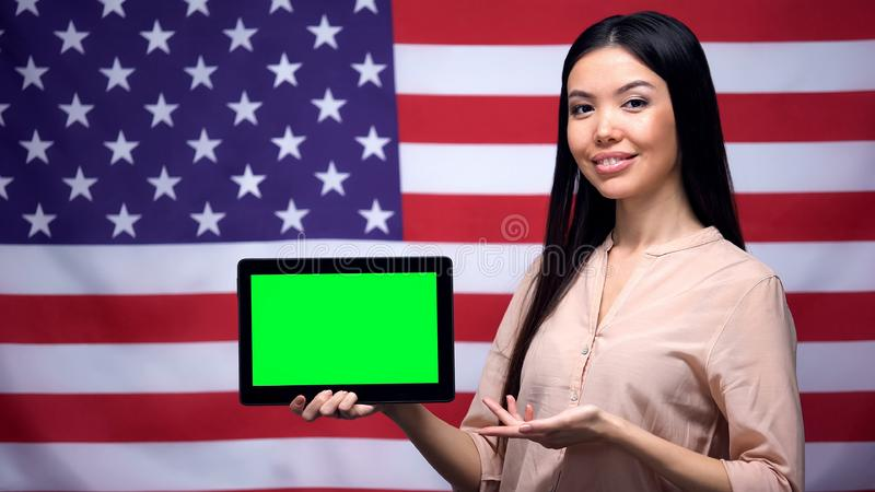 Girl holding tablet with green screen, USA flag on background, migration stock images