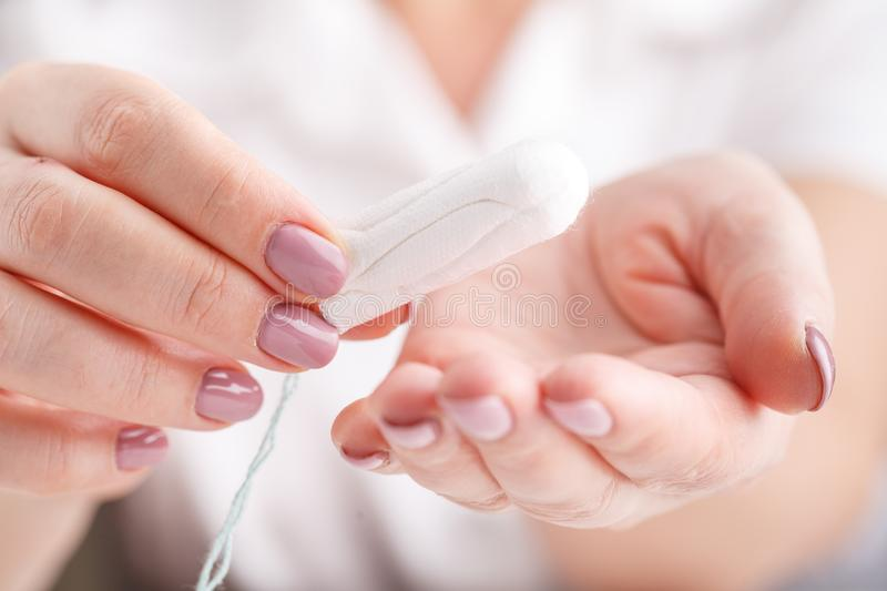 Girl holding tampon during the monthly cycle. Young woman hands stock image