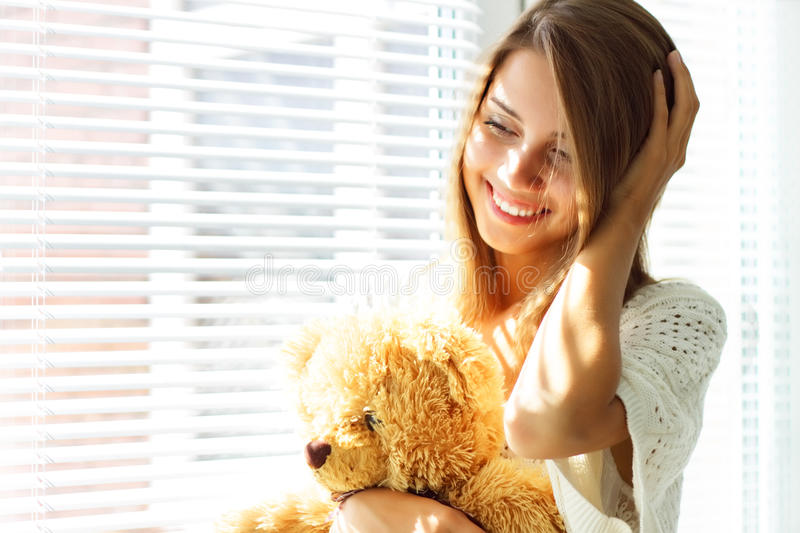 Girl holding a teddy bear. Smiling girl sitting by the window royalty free stock images