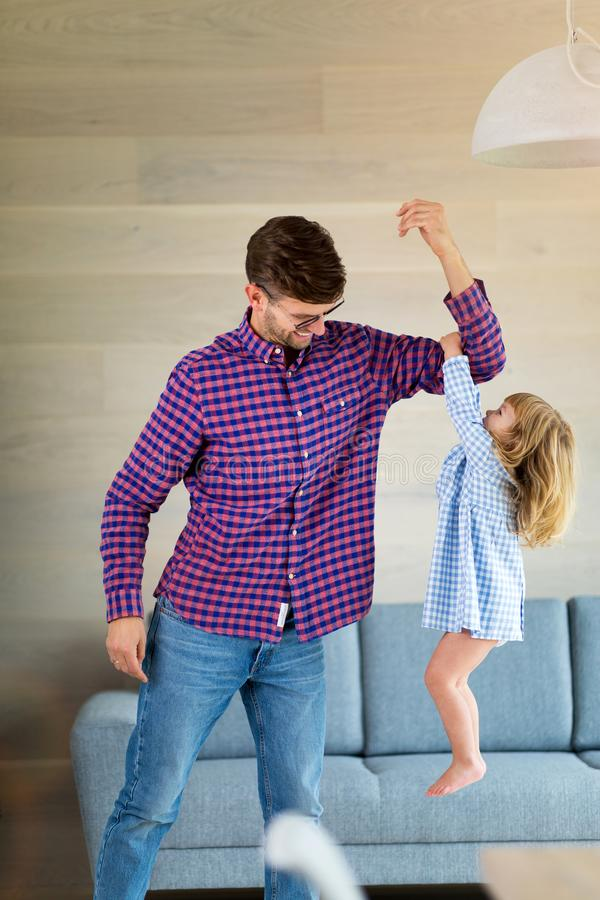 Girl holding on to her father`s arm as he lifts her up. Little girl holding on to her father`s arm as he lifts her up royalty free stock images