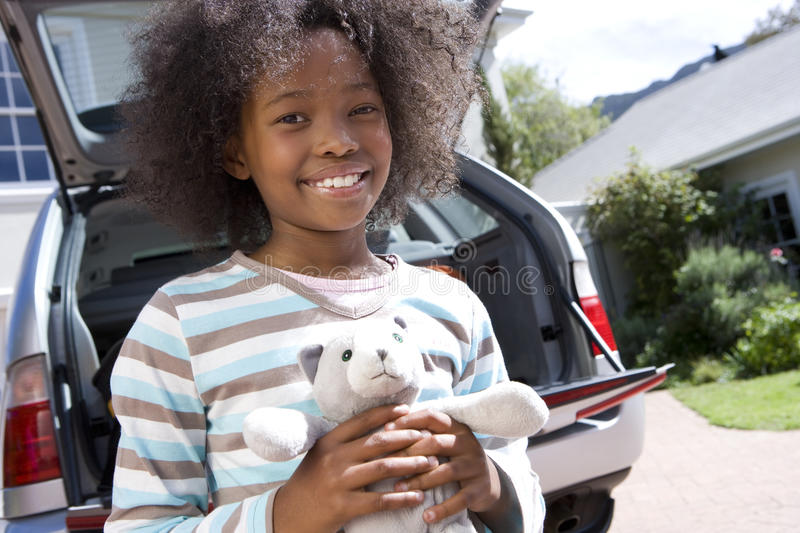 Girl (8-10) holding toy by car, smiling, portrait, low angle view royalty free stock photos