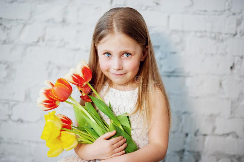 girl holding tulips in hands. Adorable smiling little girl holding flowers for her mom on mother& x27;s day stock images