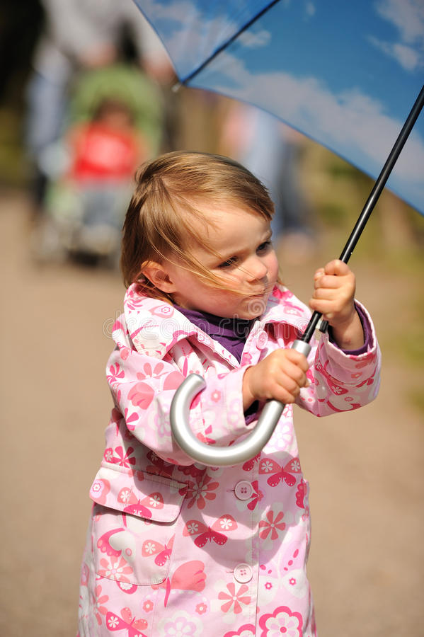 Girl holding an Umbrella. A little girl holding a big blue umbrella royalty free stock images