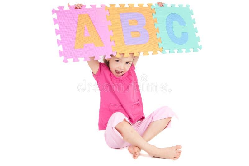 Girl holding up alphabet abc sign. Girl holding alphabet abc sign above her head. Isolated on white stock image