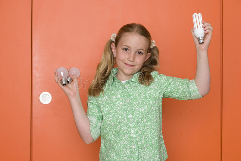 Girl (9-11) holding up light bulbs by orange door and wall, smiling, portrait stock photography