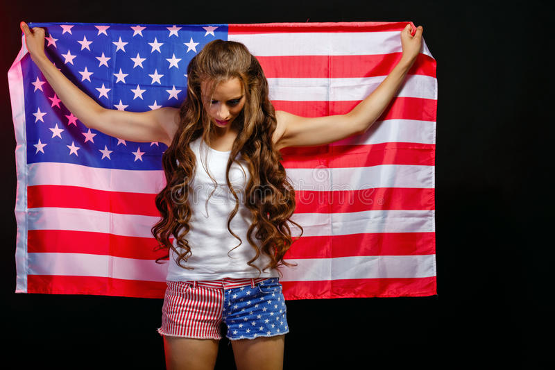 Girl holding US flag. Young attractive girl holding a US flag. She a T-shirt and shorts with a print of the flag. Long curly hair. Patriot country royalty free stock images