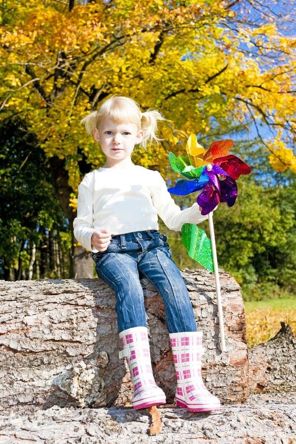 Girl holding a vane. Sitting little girl holding a vane stock photo