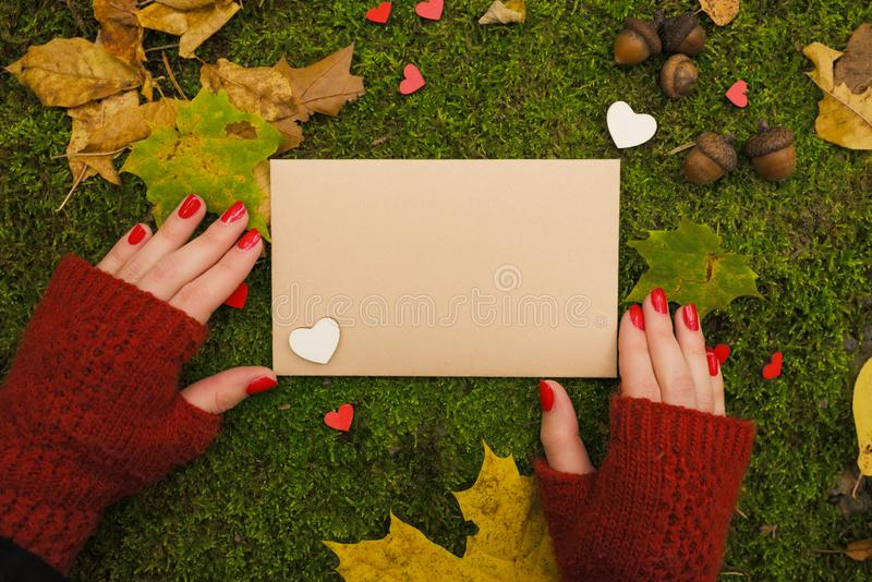 The girl is holding a vintage empty sheet of paper in autumn park. Top view stock image