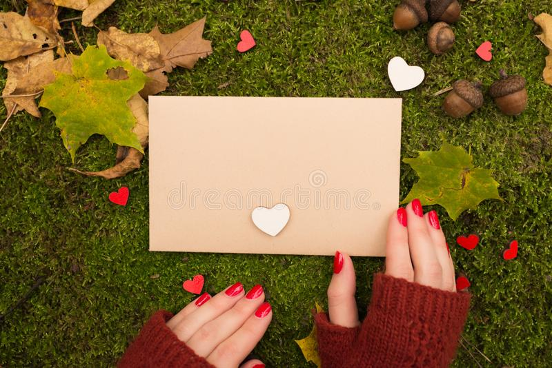 The girl is holding a vintage empty sheet of paper in autumn park. Top view stock photography