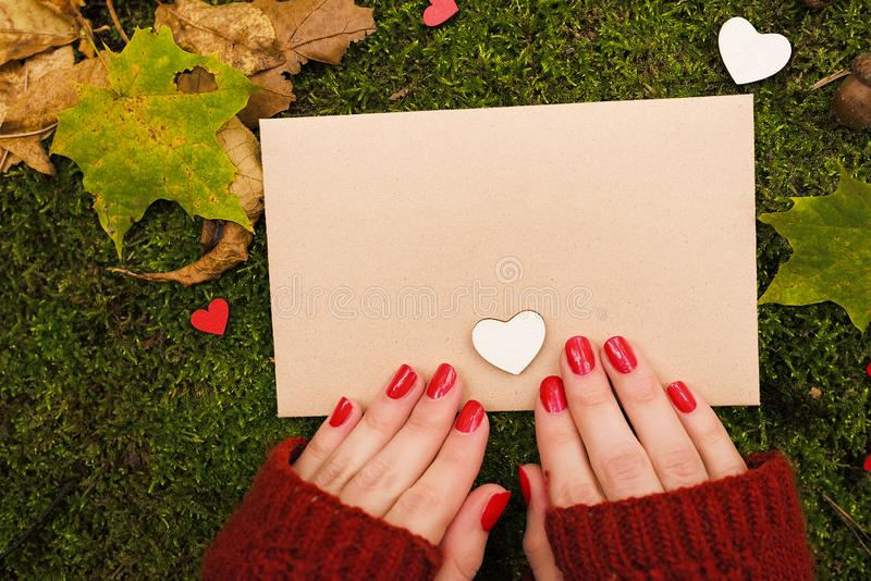 The girl is holding a vintage sheet of paper in autumn park. Top view stock photos