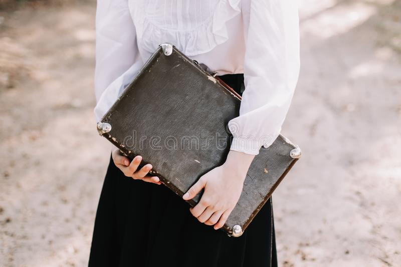 Girl with a vintage suitcase. Traveler with retro luggage. Travel concept. Girl holding a vintage suitcase. Traveler with retro luggage. Travel concept stock photo