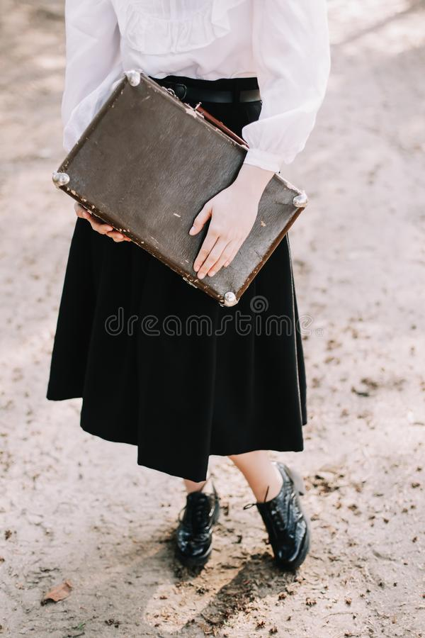 Girl with a vintage suitcase. Traveler with retro luggage. Travel concept. Girl holding a vintage suitcase. Traveler with retro luggage. Travel concept royalty free stock image
